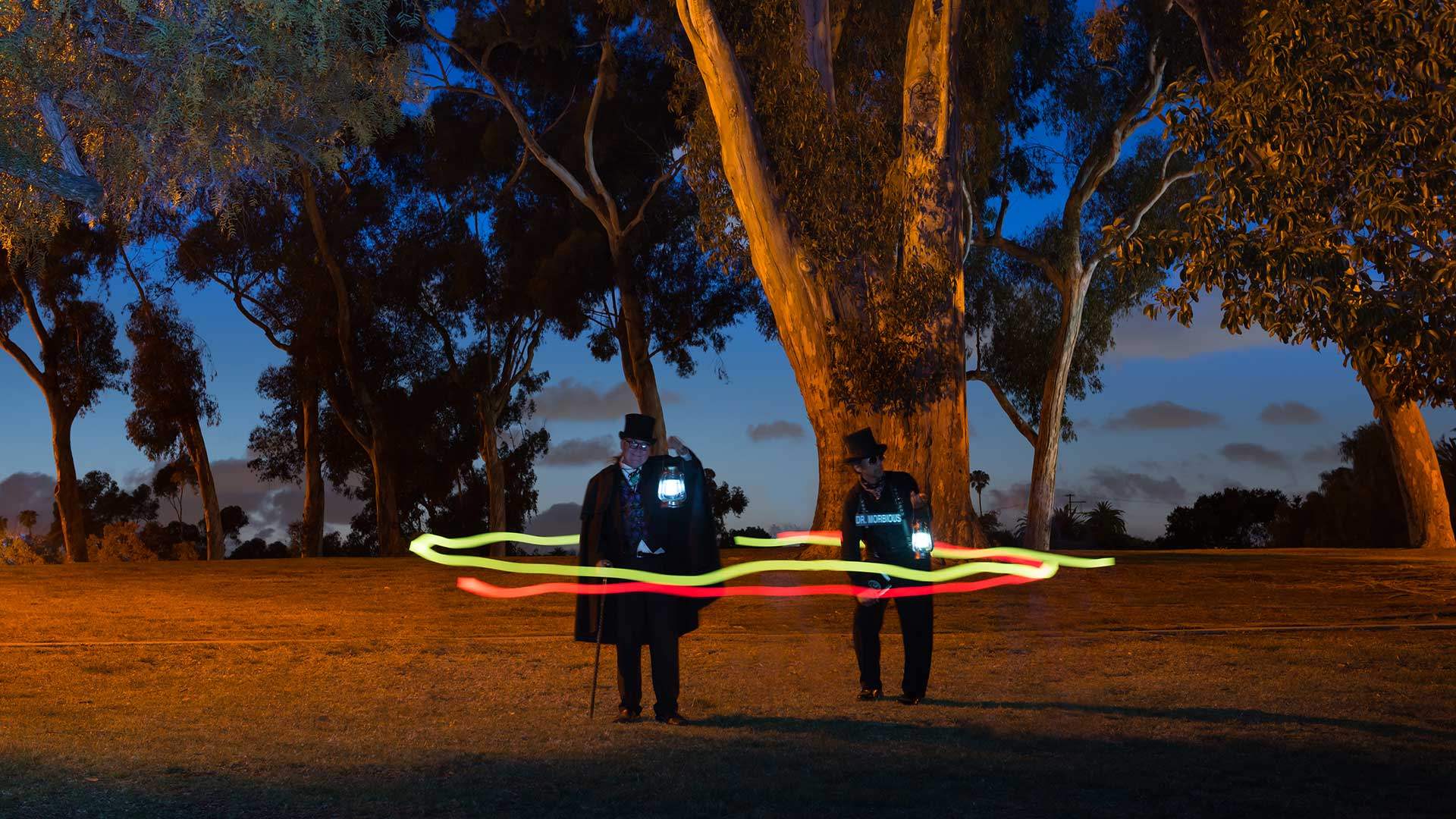 san Diego haunted forest at night with two ghost hosts standing and holding lanterns while two orbs encircle them