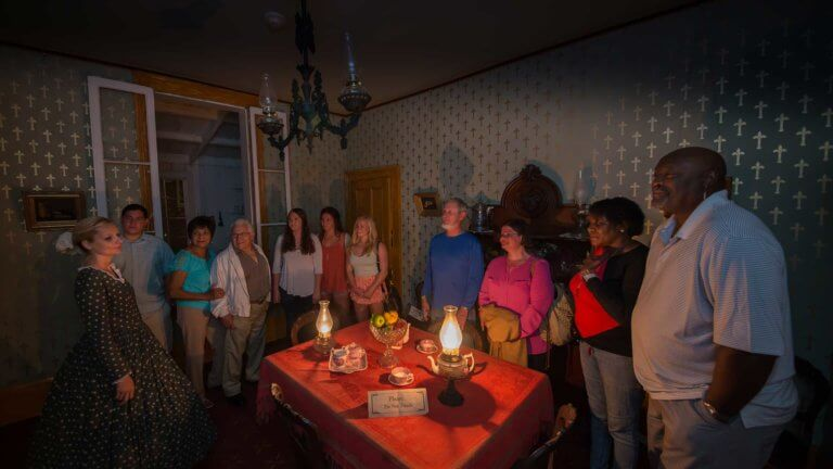 Guests and female ghost host in period costume standing in a dark room inside the Whaley House with a table in the middle that has two lanterns, a fruit bowl and plates and teacups