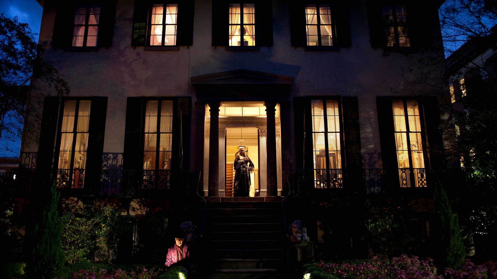 andrew low house at night with haunted tour guide at the door