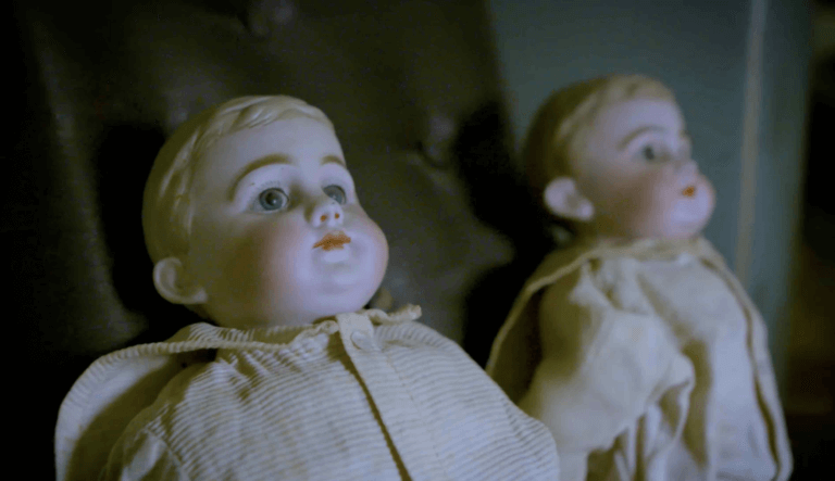 night time picture of two baby dolls with porcelain faces wearing vintage clothes and staring off to the side