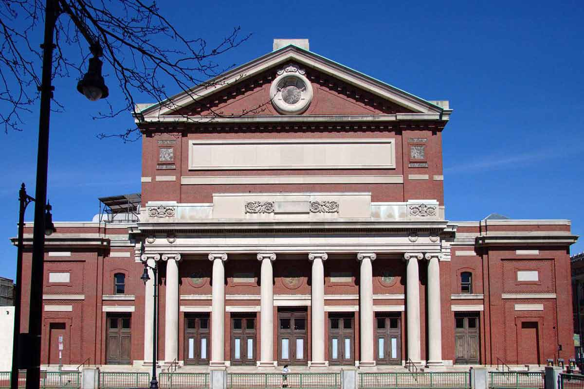 The exterior of the Boston Symphony Hall made of brick and columns in a Renaissance style