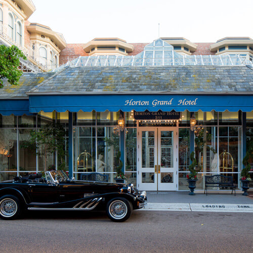 The glassed-in entrance to the Horton Grand Hotel in San Diego where a black vintage convertible automobile from the 1930s is parked near the loading zone