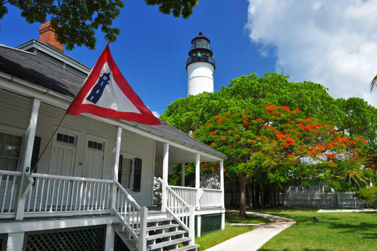 picture of old wooden house with stairs, porch, railing and windows, a flag with an icon of lighthouse in the foreground, and trees and the top of key west lighthouse in the background