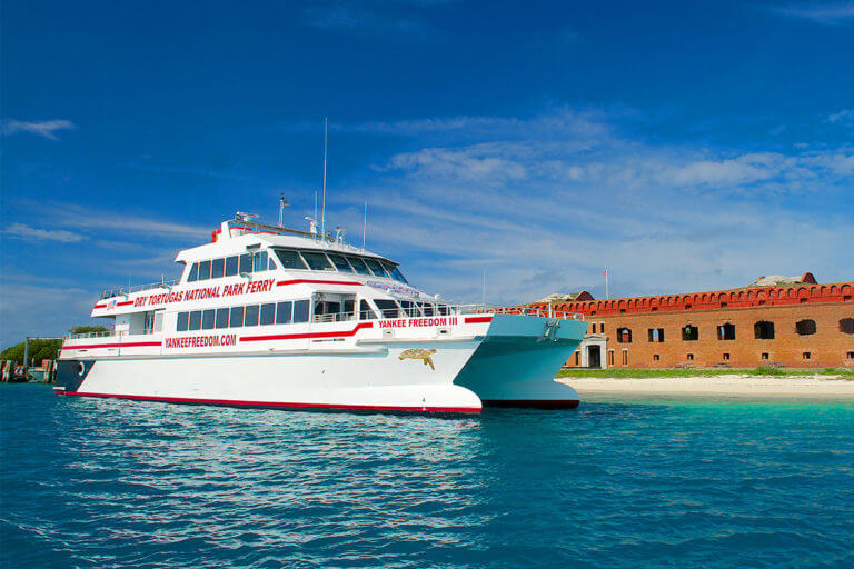 picture of a large ferry with the words 'Dry Tortugas National Park Ferry' docked in front of fort jefferson at Dry Tortugas National Park