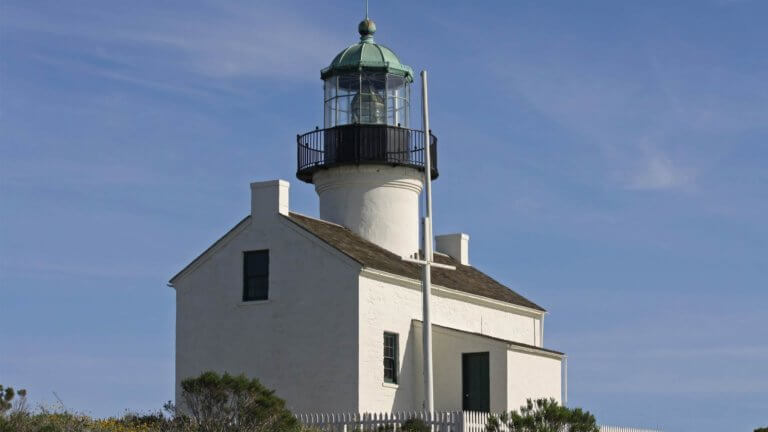picture of a small white washed house with a lighthouse jutting out