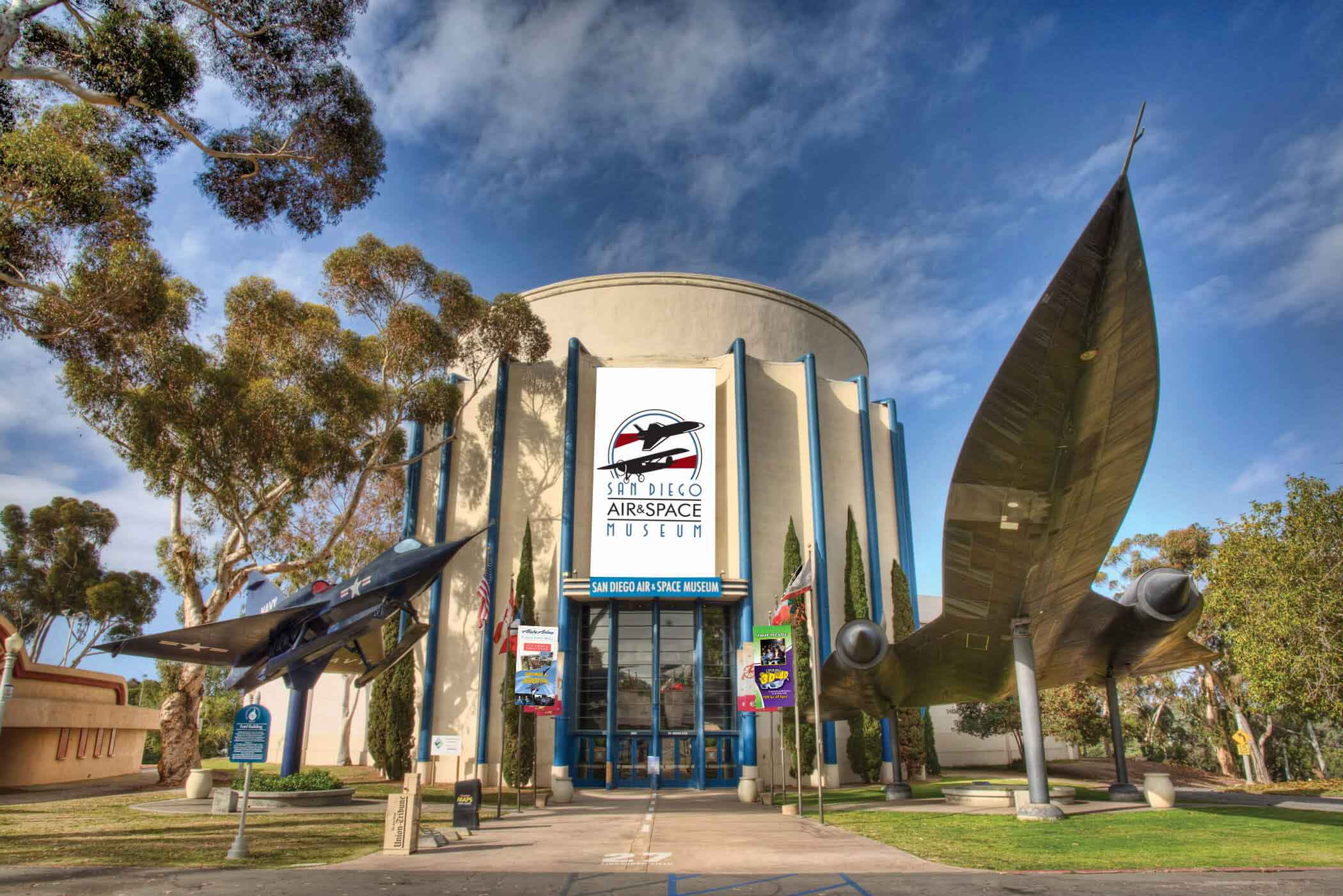 building exterior of San Diego Air & Space Museum with airplane models mounted on posts on either side of building