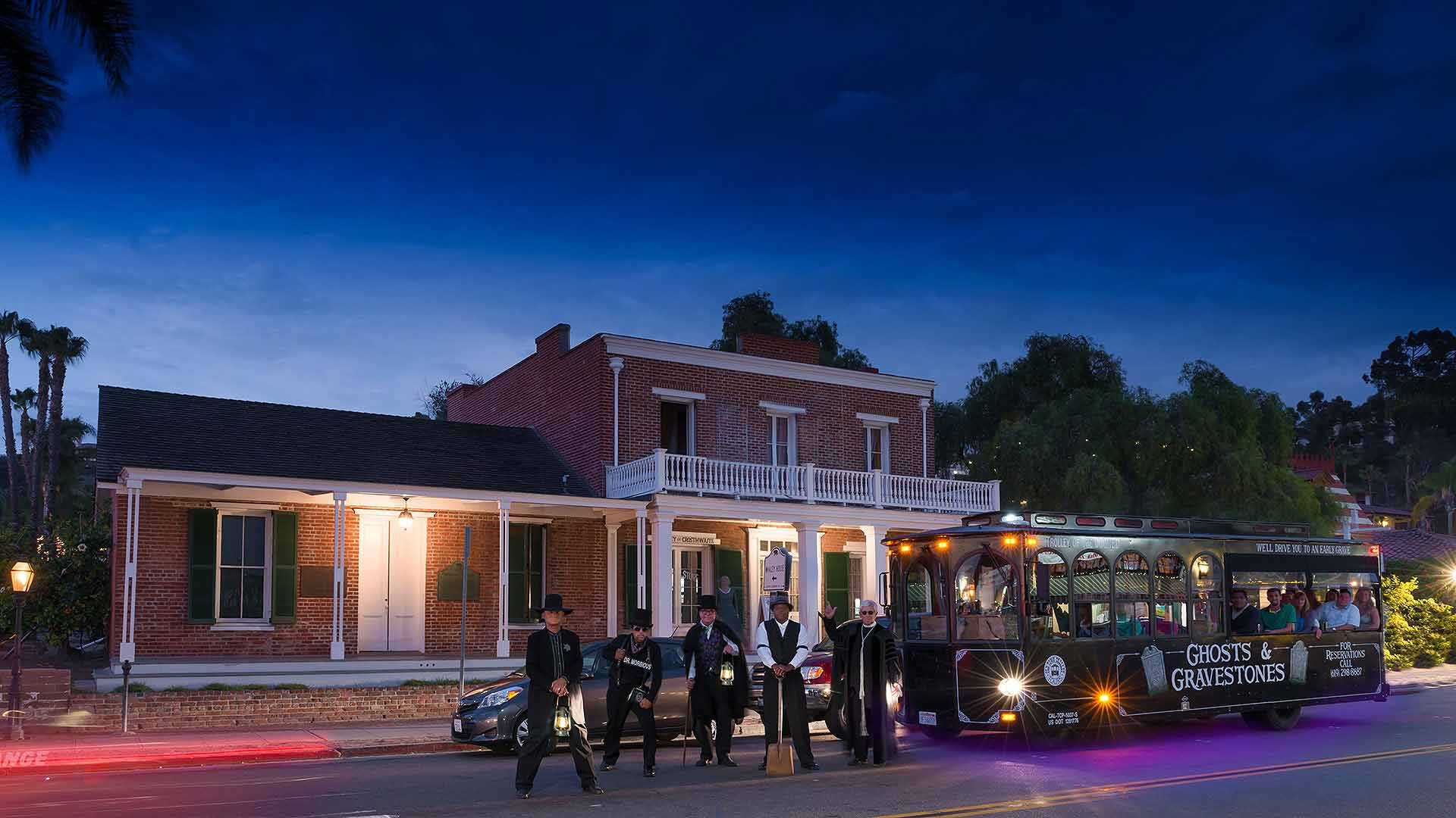 five san diego ghost hosts standing next to ghost trolley at night with the whaley house behind them