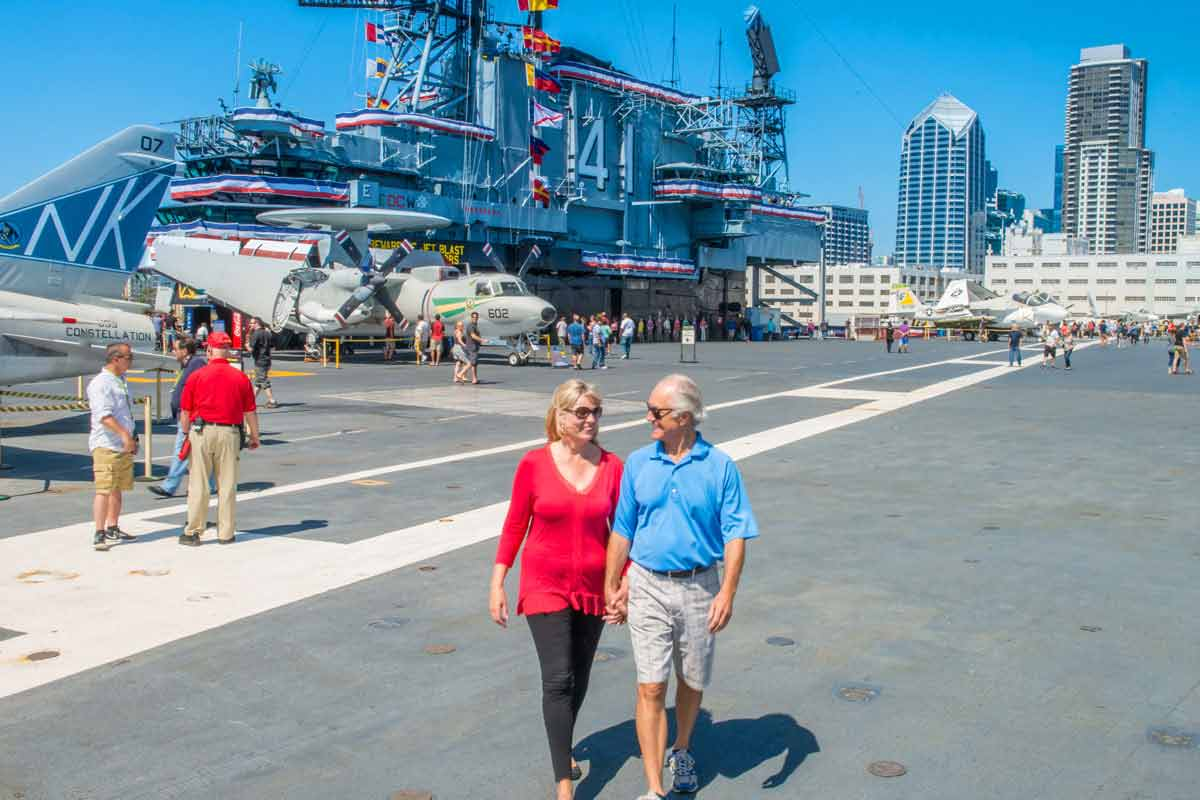 couple walking hand in hand at uss midway museum