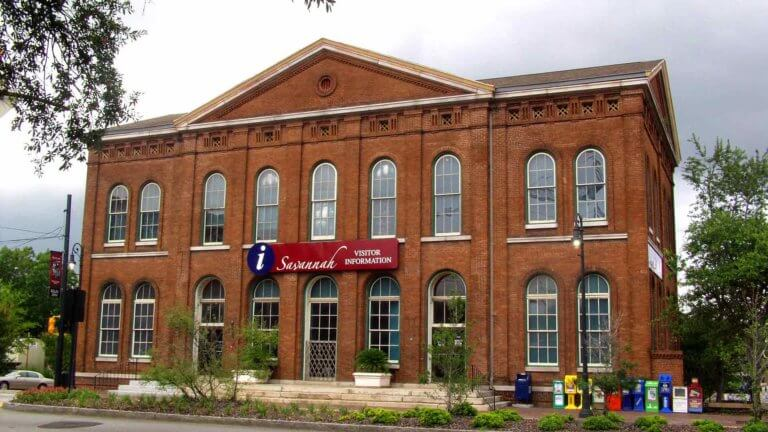 brick building exterior of Savannah History Museum with rows of windows rounded at the top and a sign that reads has an 'i' information symbol and the words 'Savannah Visitor Information'