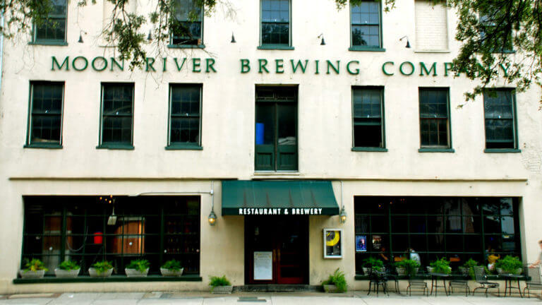 building exterior with two rows of windows on top two floors, the words 'Moon River Brewing Company' between second and third floor, two wooden doors with large windows on either side on first floor, and an awning over the doors that reads 'Restaurant & Brewery'