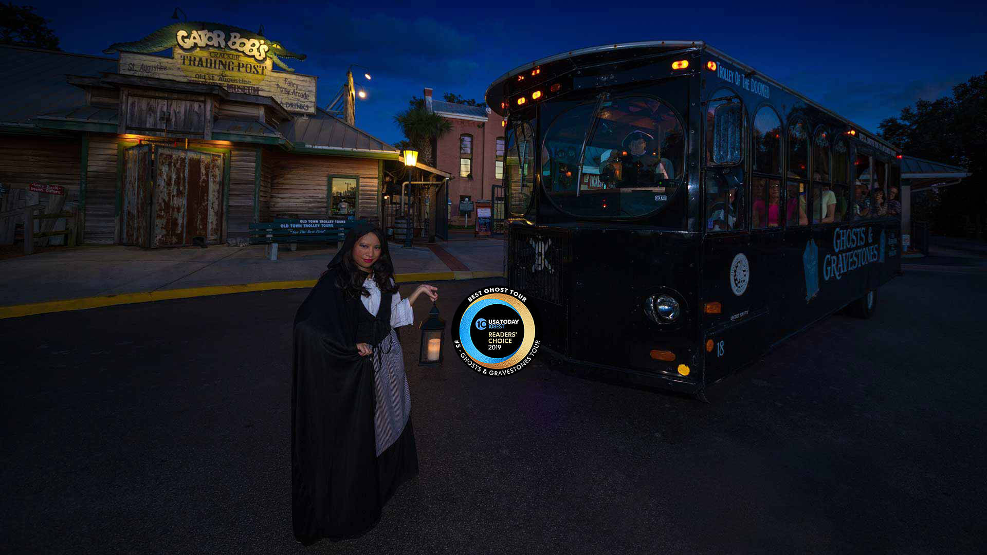 night time picture of ghost trolley in front of St. Augustine Old Jail, a female ghost host standing to the left and a Round logo that reads USA Today 10 BEST READERS' CHOICE 2019' and around logo, the words 'BEST GHOST TOUR, #5 - GHOSTS & GRAVESTONES TOUR'