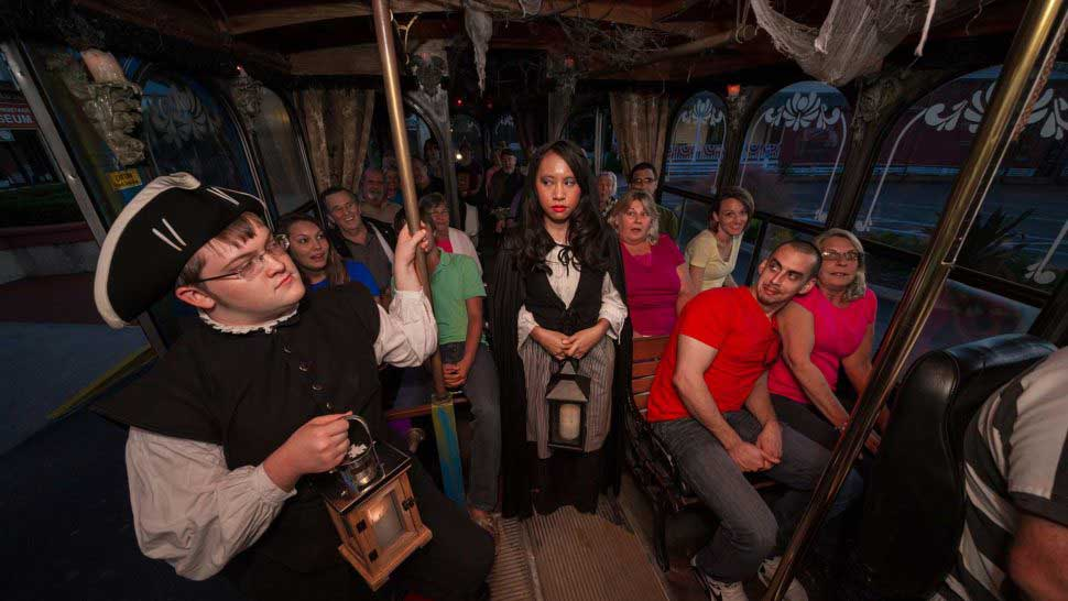 tour guides dressed in costume stare at each other on ghost tour trolley