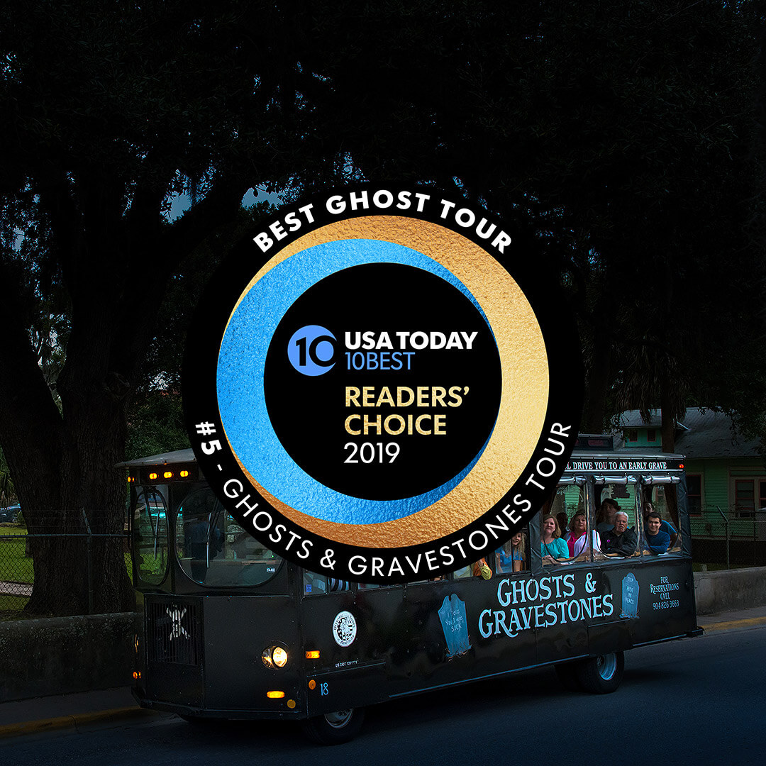 St. Augustine trolley at night driving past a cemetery and in the foreground, Round logo that reads USA Today 10 BEST READERS' CHOICE 2019' and around logo, the words 'BEST GHOST TOUR, #5 - GHOSTS & GRAVESTONES TOUR'