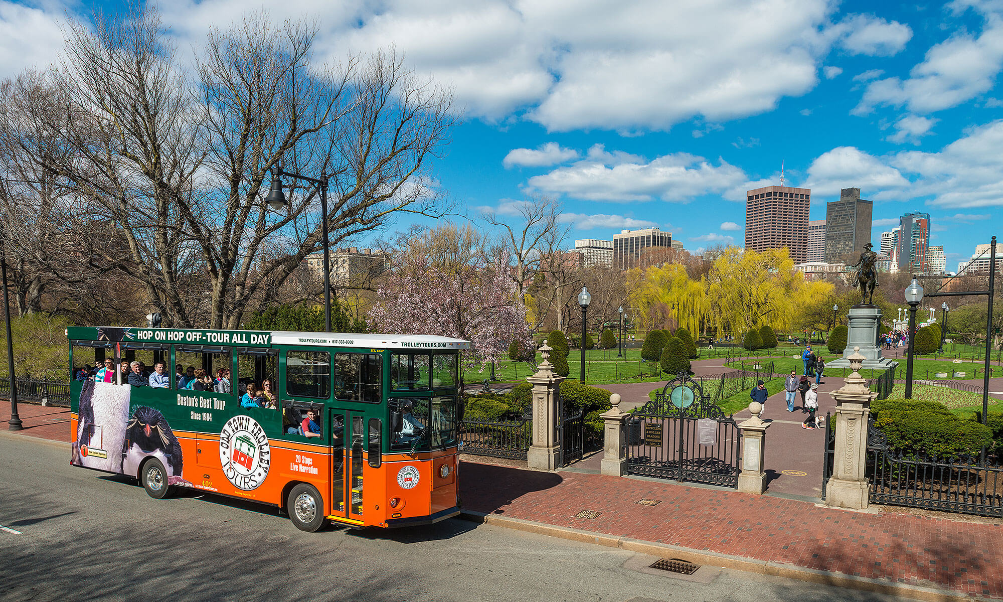 old town trolley in Boston driving past Boston Public Garden and George Washington Statue and city skyline in background