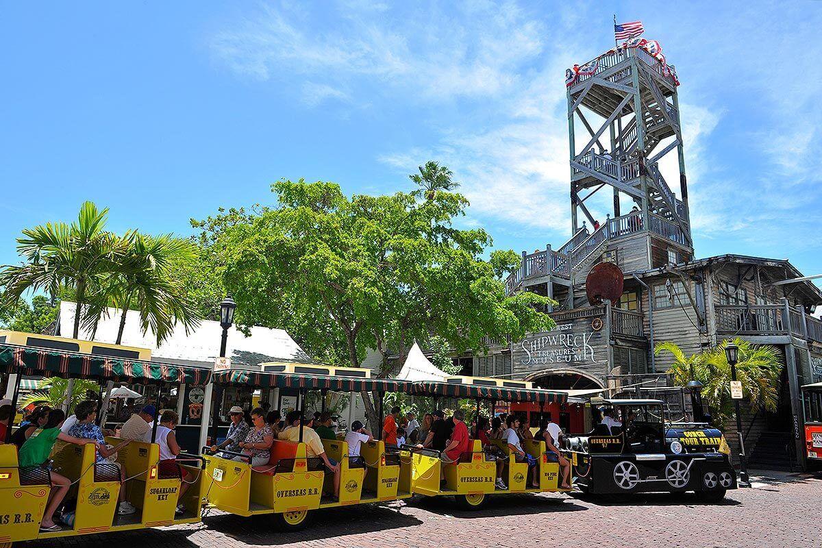 Key West Conch Tour Train driving past Shipwreck Museum